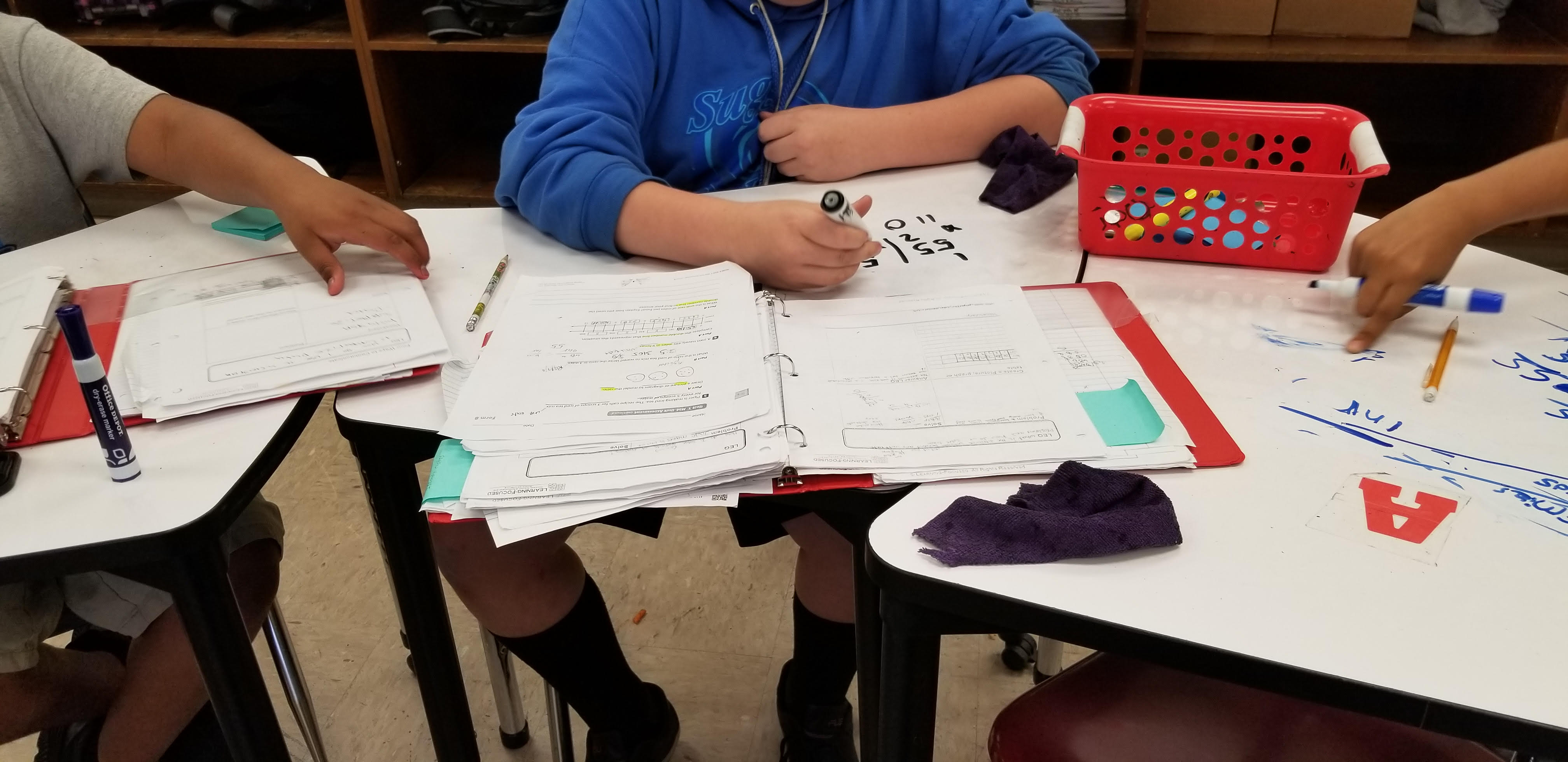 Students writing and talking about math.